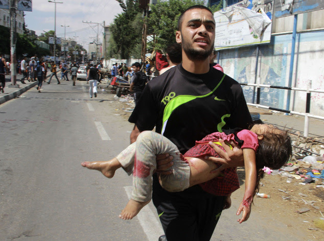 A Palestinian man carries a child killed in a blast outside a UN run school in Rafah, in the southern Gaza Strip, Sunday, Aug. 3, 2014. UNRWA's Director of O...