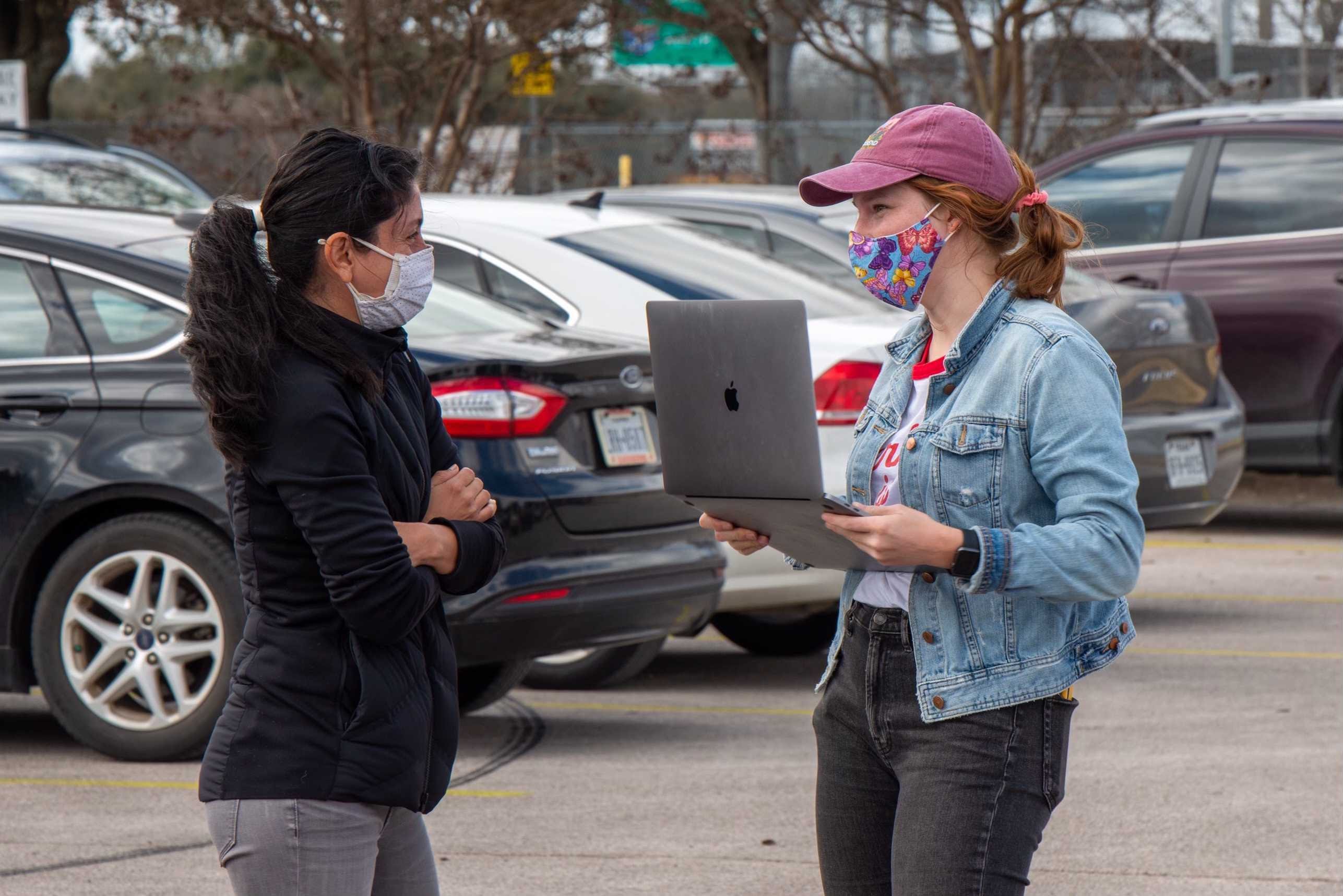 Powered by People volunteer wearing a mask with a clipboard, signing in volunteers to distribute water in Austin, Texas