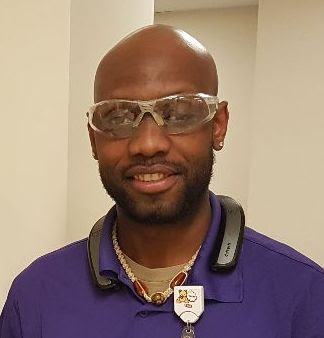 Jean in his purple uniform and safety glasses at his workplace