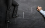 Businessman climbing the career steps drawn on a black chalkboar