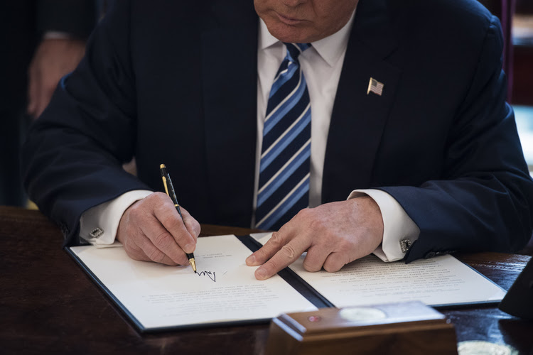 Trump signs executive orders in the Oval Office last week. (Jabin Botsford/The Washington Post)</p>