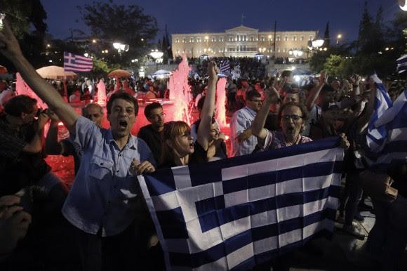 Los resultados oficiales del referéndum apuntan a una clara victoria del 'no' con el 61,24 por ciento de los votos, mientras que el 'sí' logra el 38,76 por ciento de los sufragios, según datos correspondientes al 52,97 por ciento del escrutinio. En la imagen, partidarios del 'no' se concentran en la plaza Syntagma en Atenas. Foto: YANNIS KOLESIDIS (EFE/EPA)