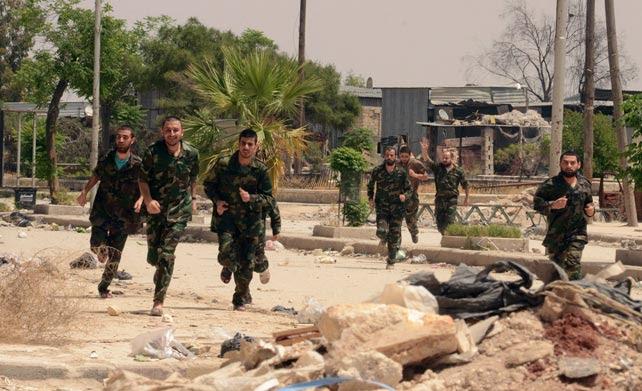 Soldado del Ejército sirio celebran su liberación por los rebeldes como parte del acuerdo entre el presidente Al Assad y los insurgentes con el que se retiran del casco viejo de Aleppo.