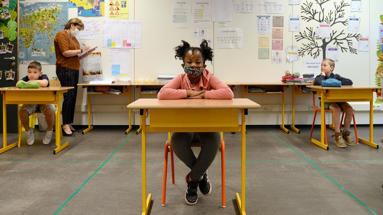 A schoolchild and a teacher wear protective face masks in a classroom at a flemish primary school during its reopening as a small part of Belgian children head back to their schools with new rules and social distancing during the outbreak of the coronavirus diseasein Brussels, Belgium, May 15, 2020.