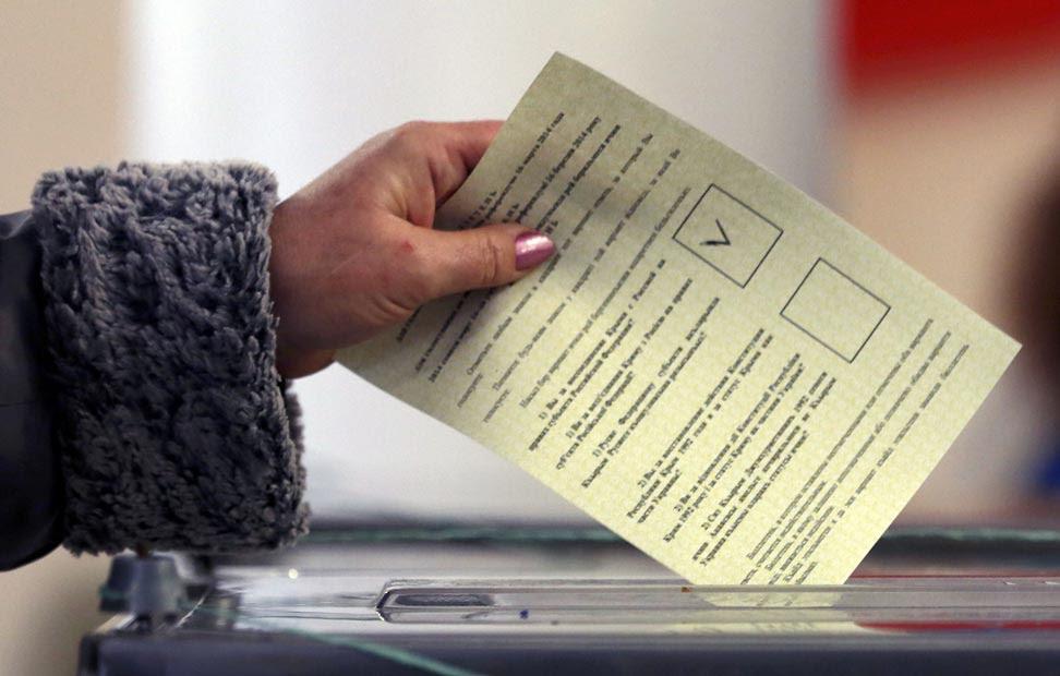 Una mujer introduce su voto en una urna electoral.