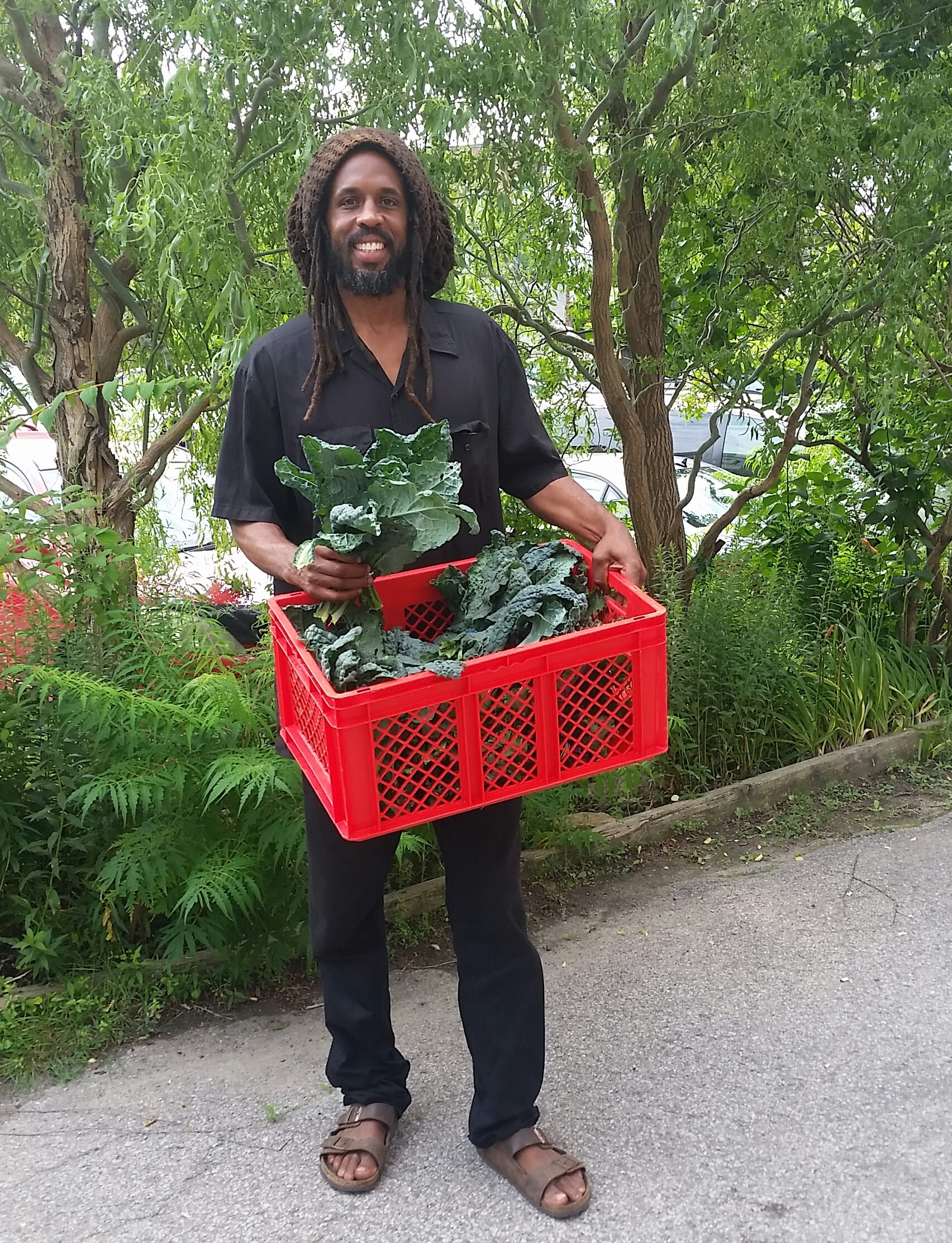 Shabaka standing tall and smiling with beard, dreadlocks, and a crate of crisp kale