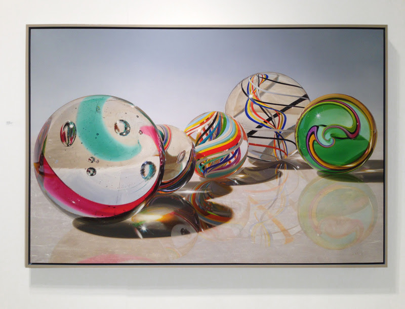 Steve Mills, FAMILY, Oil on Panel, 40 x 60 inches; a collection of brightly hued marbles