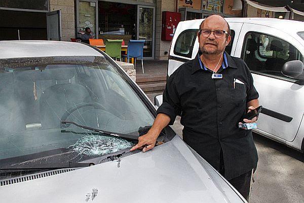 Israeli journalist Aharon Granot shows his smashed windshield, damaged in a stoning attack by Arab terrorists near the Judea city of Halhul, in Gush Etzion. (October 22, 2015)