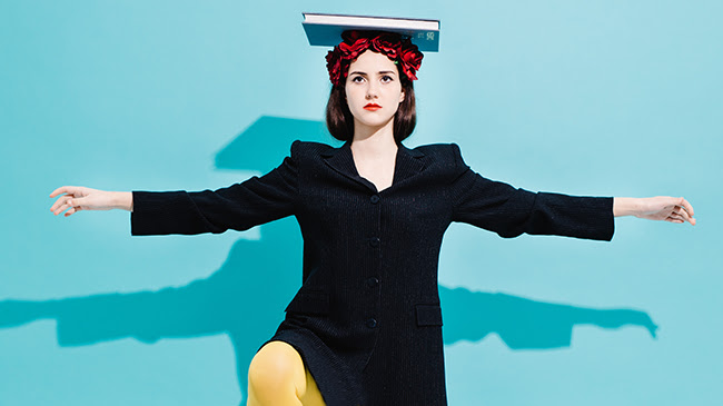 Woman balancing a book on her head standing on one foot