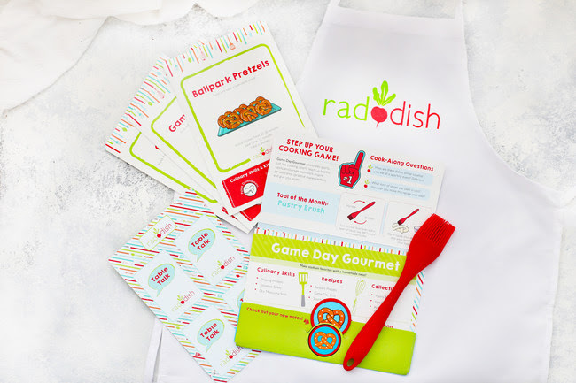 "The new Raddish folder introduces the kit's theme, stores all of the kit's contents, displays the collectible apron patch, announces the tool of the month, features games/activities and shares how to access ""Bonus Bites""-the expansive library of free online content."