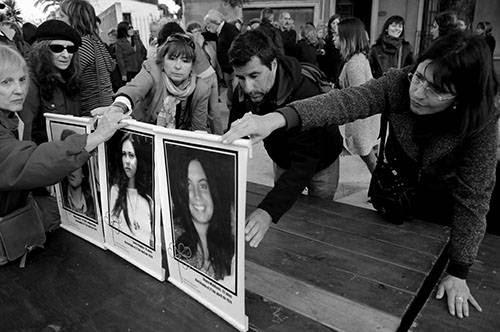"""Participantes del acto de inauguración de la Marca de la Resistencia, en recuerdo de las """"Muchachas de abril"""", colocan, ayer, sus fotos en el estrado. / Foto: Javier Calvelo"""