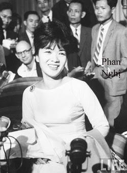 Bà Trần Lệ Xuân cười lần cuối trong buổi tối Tháng 10 năm 1963 ở Phòng VIP Phi trường Tân Sơn Nhứt. Người complet-veston đứng sau Bà là Ký Phan Nghị, phóng viên Nhật báo Ngôn Luận. Trong ảnh này Bà Trần Lệ Xuân đã đứng lên, áo lạnh và sắc ở tay, để đi ra phi cơ PanAm American.