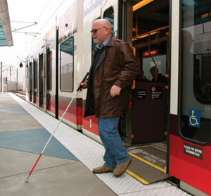 Photo of man with white cane exiting a light rail car.