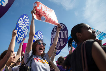People celebrate during a rally at the Supreme Court in Washington, Monday, June 27, 2016, after the court struck down Texas' widely replicated regulation of abortion clinics.
