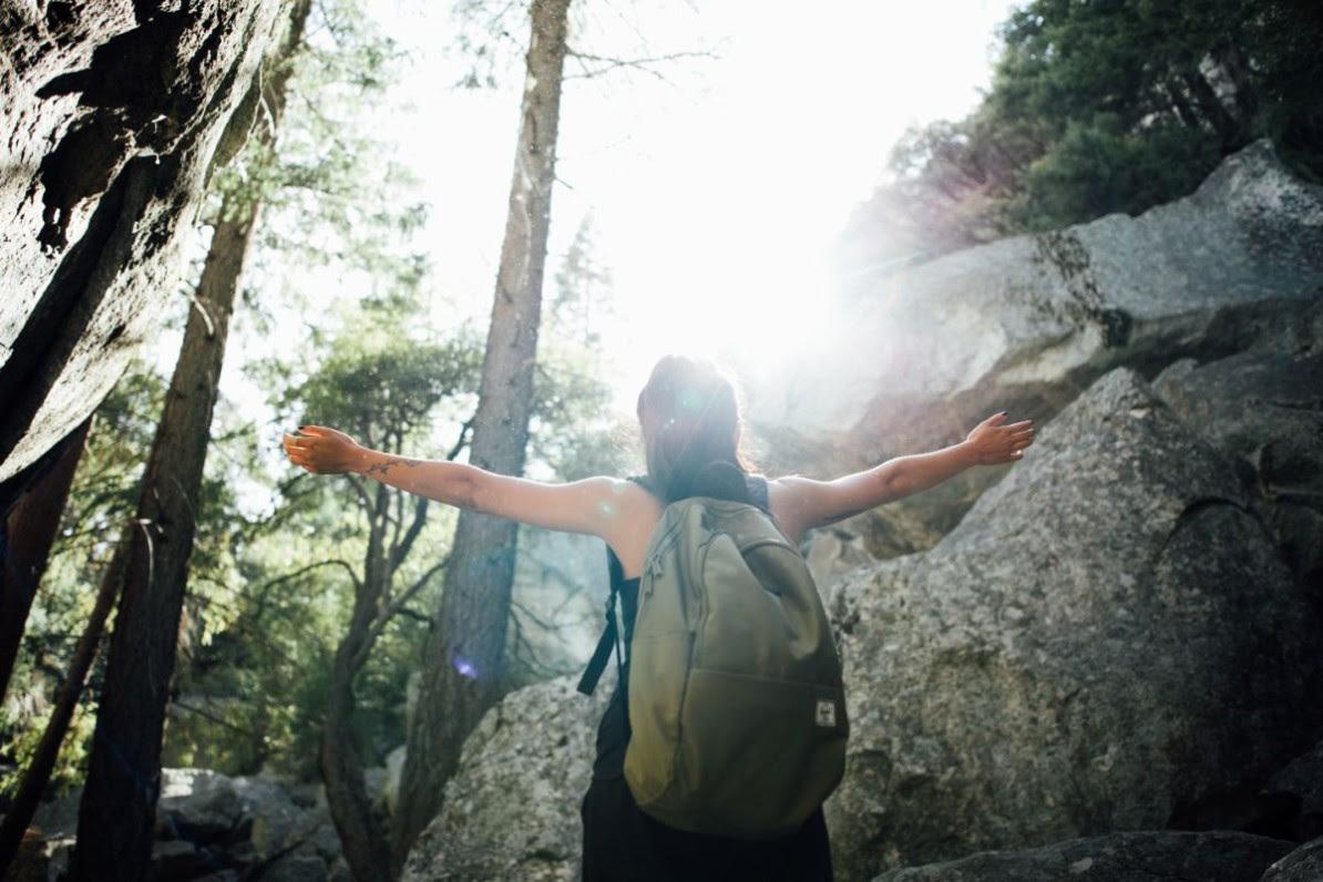 Människa med ryggsäck i skog som tittar upp mot solen
