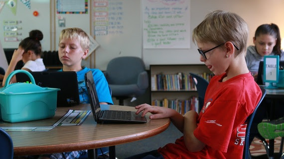 Two fourth-grade boys sit at a table in their classroom looking at laptops in which they are taking the training test for Wyoming's new statewide assessment. One of them has his tongue sticking out slightly in a look of concentration.