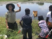 Park Ranger standing in water in front of class and waving at the camera
