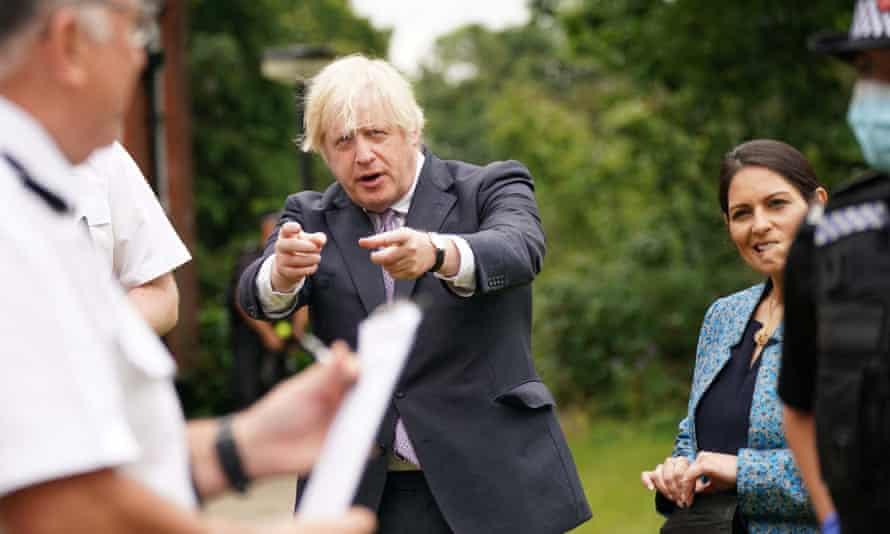 Boris Johnson (centre) with home secretary, Priti Patel, in Surrey as the government released new proposals to tackle crime.