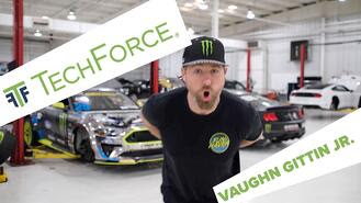 """Video thumbnail for Vaughn Gittin, Jr.'s shout-out for TechForce's peer network. Vaughn is standing in a well-lit, white autoshop with racecars behind him. The words """"TechForce"""" and """"Vaughn Gittin, Jr."""" appear in green letters over white boxes on screen."""