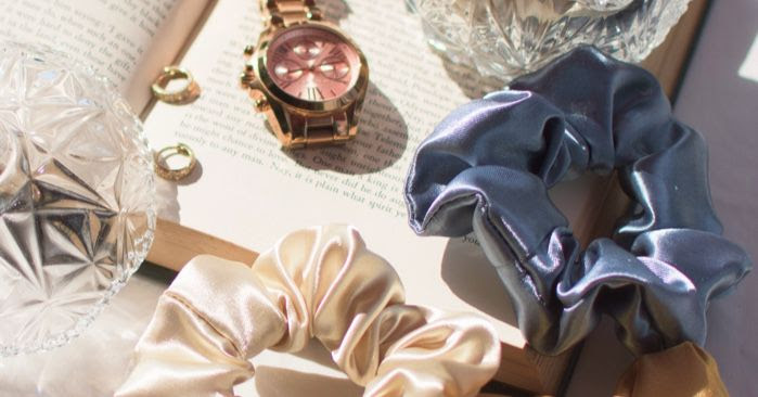 1990s satin scrunchies and rose gold watch on top of a book