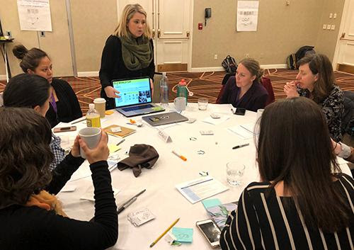 Woman stands at conference table showing laptop as other attendees look on