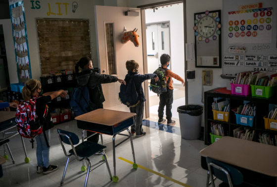 Kindergarten students line up with their arms stretched out in front of them to maintain social distance with their peers, inside a classroom at Stark Elementary School on October 21, 2020 in Stamford, Connecticut.
