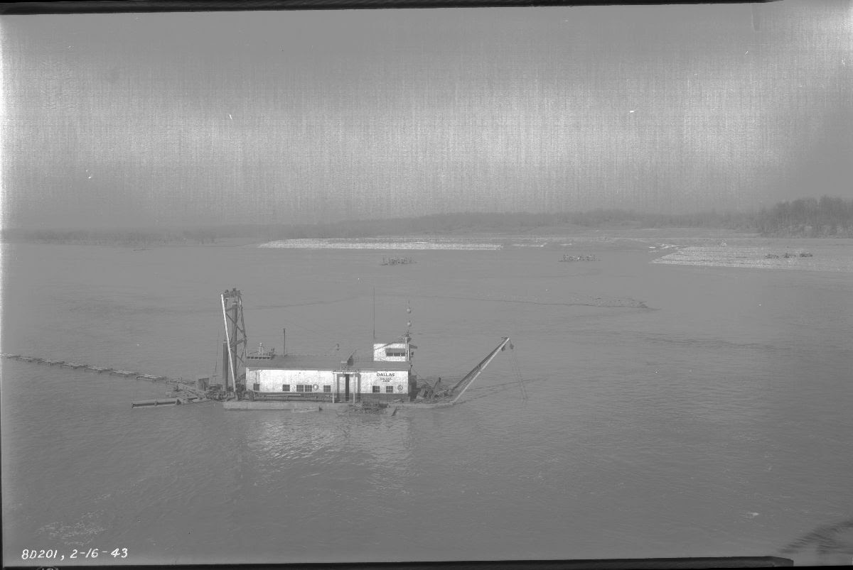 Black and white photograph of a river channel just below the dam site. A barge is floating in the middle of the river