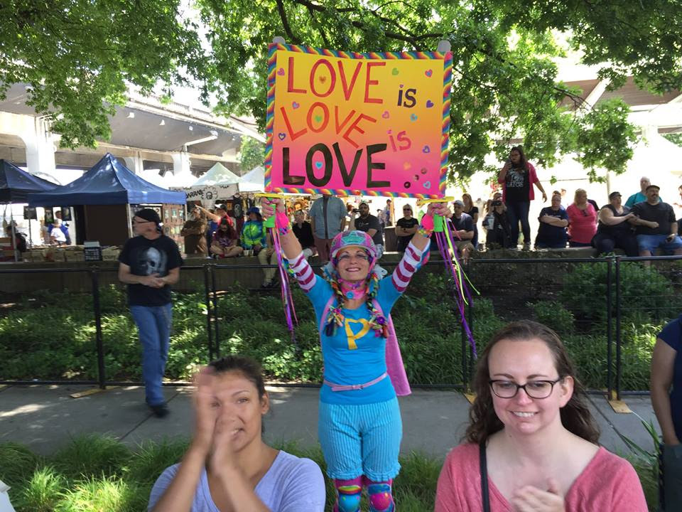 "Parade goers at Portland Pride festival carrying a sign reading ""Love is love is love."""