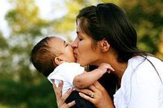 photo of a woman kissing her infant child