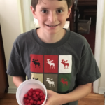 Jeremy happily displays some of the wineberries we collected over the weekend.