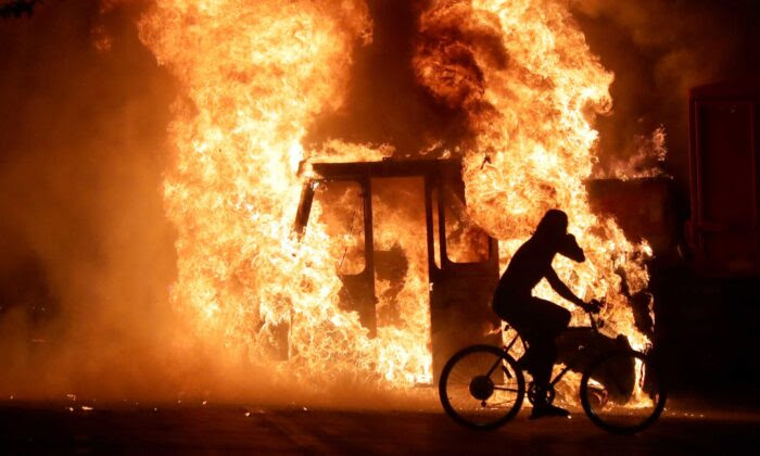 A man on a bike rides past a city truck on fire outside the Kenosha County Courthouse during riots following the police shooting of Jacob Blake in Kenosha, Wis., on Aug. 23, 2020. (Mike De Sisti/Milwaukee Journal Sentinel via USA TODAY via Reuters)