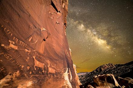 Photograph of a glowing desert sky in night. There is a huge red rock wall on the left that contains petroglyphs of animals. The right side of the image shows a yellowish brown star-studded sky and part of a mountan.