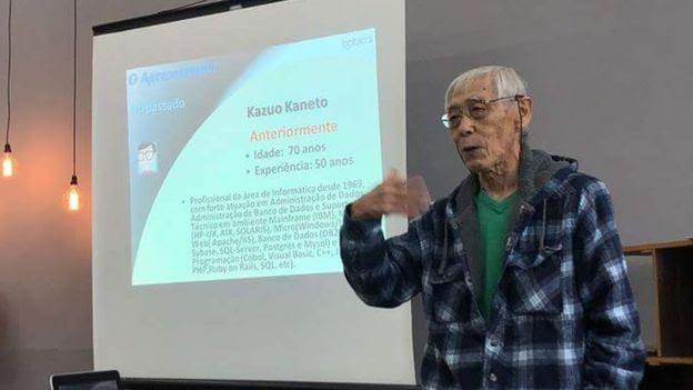 Kazuo Kaneto dá palestra, apresentando slide em tela