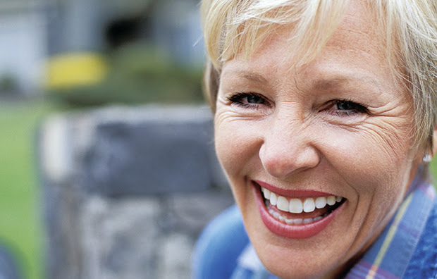 A mature woman smiling.