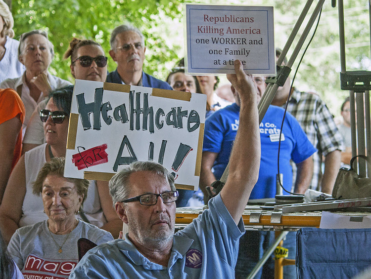 People hold up political signs at the 137th annual Fancy Farm picnic in Graves County, Ky. (Kat Russell /Paducah Sun/AP)