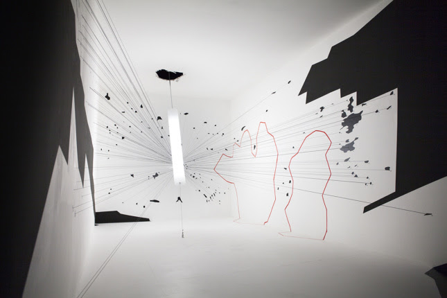 A white room with black cutouts and splatter, as well as red outlines. A cylinder comes out of a hole in the ceiling to which lines are attached.