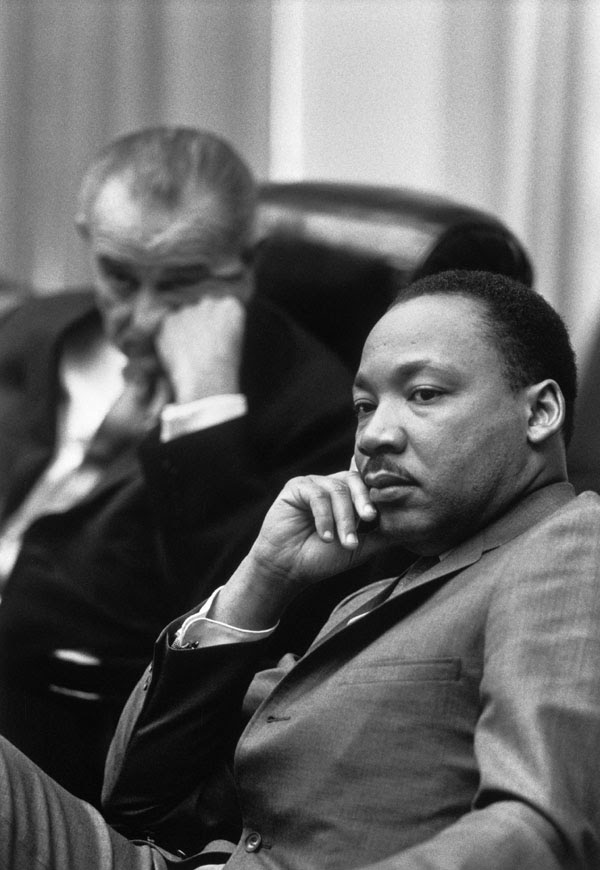 """Rev. Martin Luther King, Jr.; Presiden Lyndon Johnson in background."""