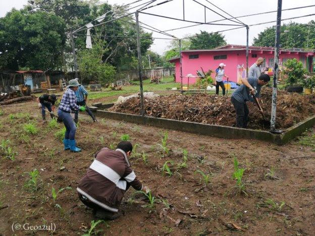 Hombres y mujeres trabajan la tierra y mezclan abono (© Geoazul)