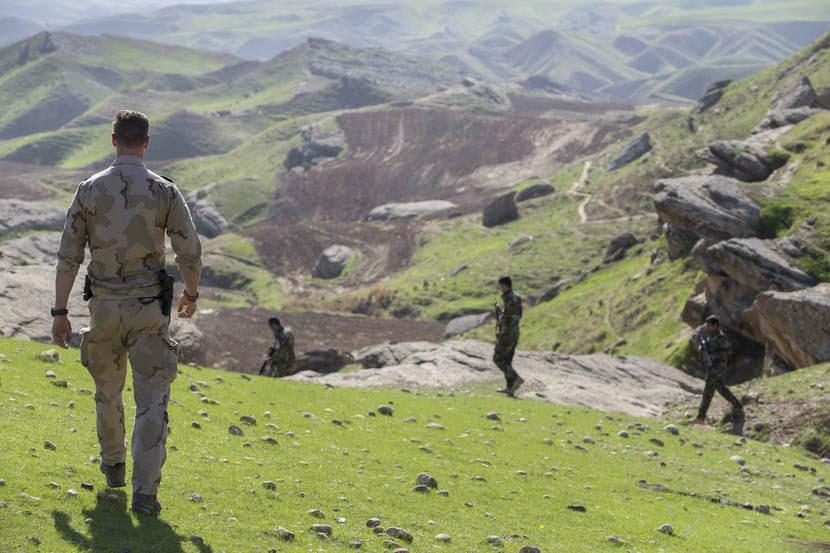 Nederlandse militaire trainer kijkt in groen berglandschap toe hoe Iraakse militairen oefenen.