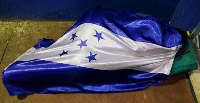 Uno de los migrantes durmiendo arropado por la bandera de Honduras. / Reuters