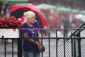 A racing fan cowers in the rain at Saratoga Race Course
