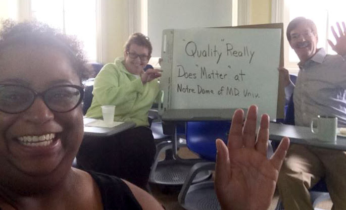 three people with a sign that says quality really does matter at notre dame of MD univ and waving at camera