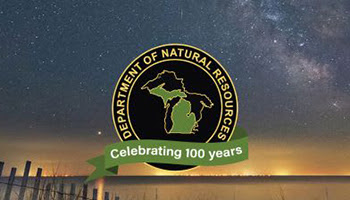 Michigan Department of Natural Resources 100 year logo against a starry sky