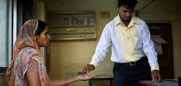 Photo of a community Health Worker distributing anti-malarial medicine.