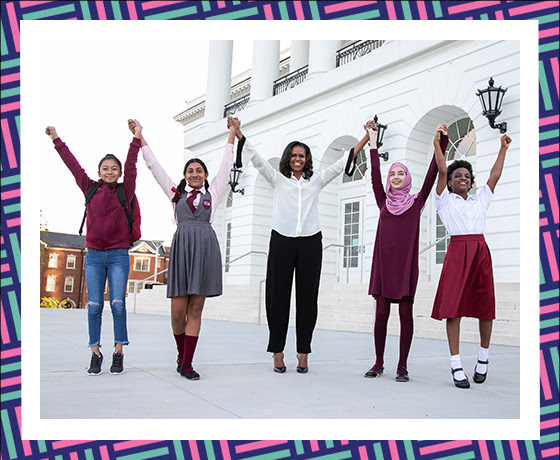 Mrs. Obama stands with arms raised with 4 girls from around the world.