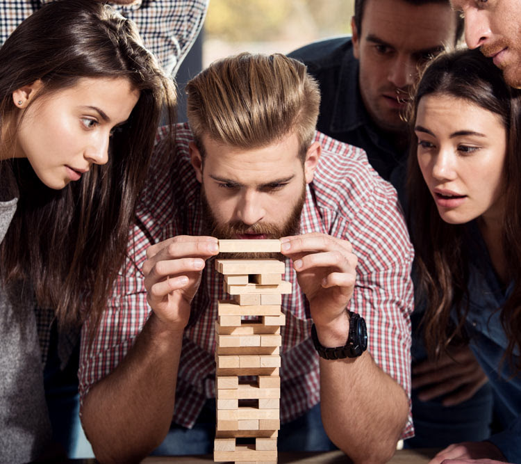 group of people playing the wooden block game Jenga