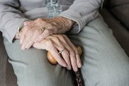Elderly lady sat with hands in her lap