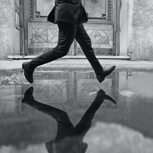 black and white image of man stepping over a puddle that he's reflected in