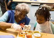 Senior Corps Foster Grandparent Virginia McLaurin helps a child with her lunch in 2016.