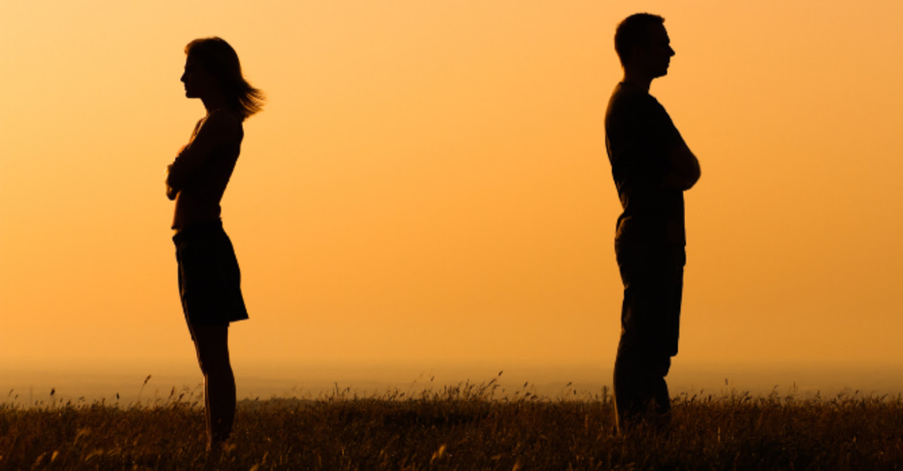 Couple standing apart with their backs to each other and arms crossed are silhouetted against the sunset